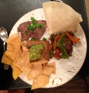 Dinner -- Carne asada, beans, peppers, a tortilla, chips, and guacamole