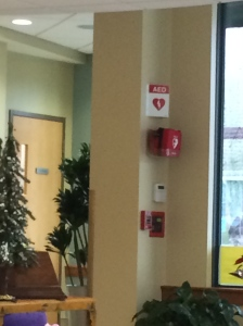 The AED is conveniently located across from the desk, (where bills are delivered and paid)