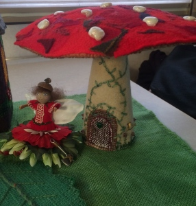 Close up of a fairy, her hatchet, and the toadstool.